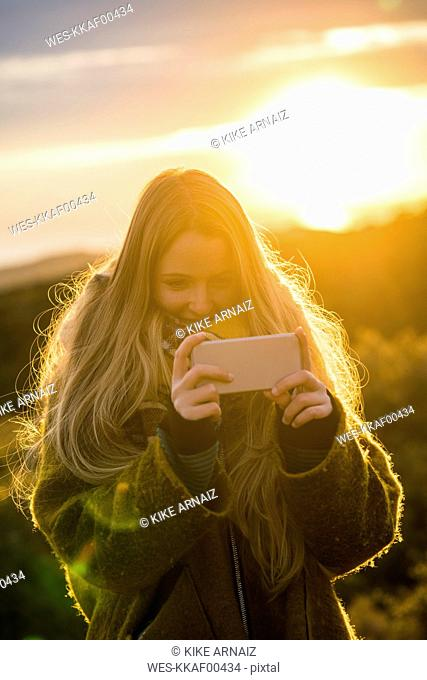 Young woman in nature taking a selfie at sunset