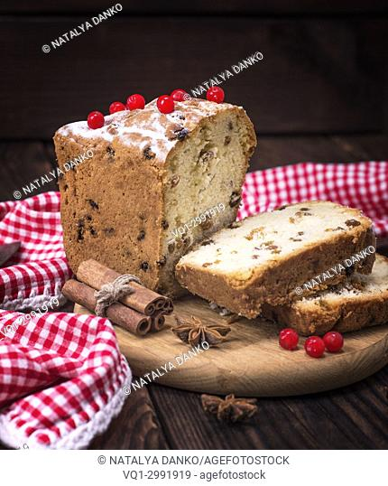 bread cake with raisins and dried fruit is sliced on brown wooden table, close up