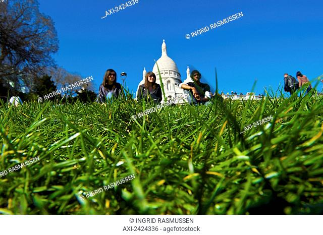 Sitting on the grass with a view of a building's white dome roof in the background; Paris, France