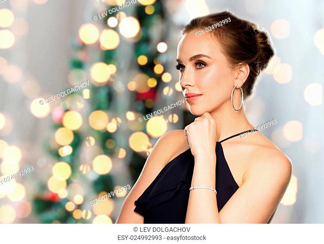 people, luxury, jewelry and holidays concept - beautiful woman in black wearing diamond earrings and bracelet over christmas tree lights background
