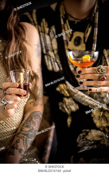 Close up of Caucasian women drinking cocktails