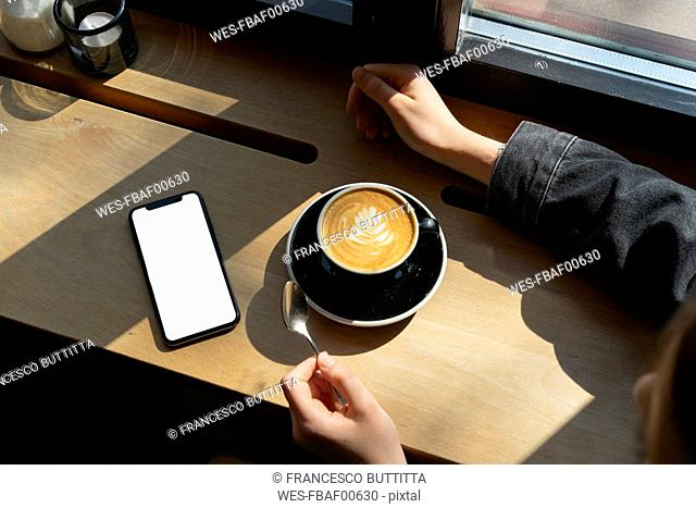 Young woman with cup of coffee and smartphone in a coffee shop