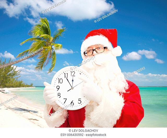 christmas, holidays and people concept - man in costume of santa claus with clock showing twelve over tropical beach background