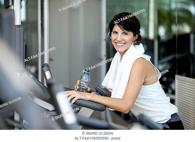 Woman hydrating after a workout, smiling