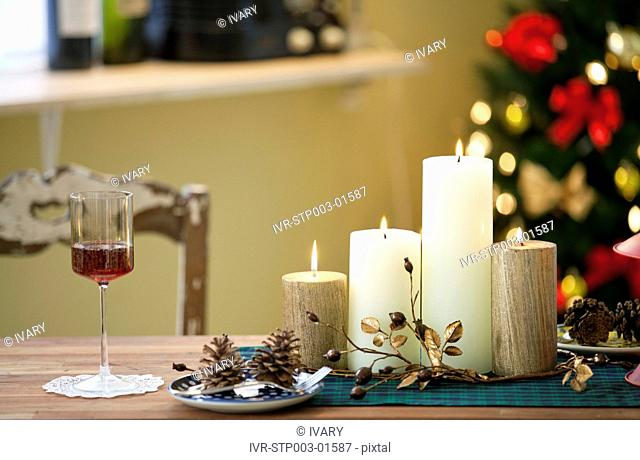 Christmas Candle And Wineglass On Table In Front Of Decorative Christmas Tree