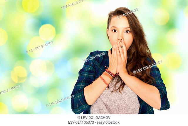 people, emotion, expression and teens concept - scared or surprised teenage girl over green holidays lights background