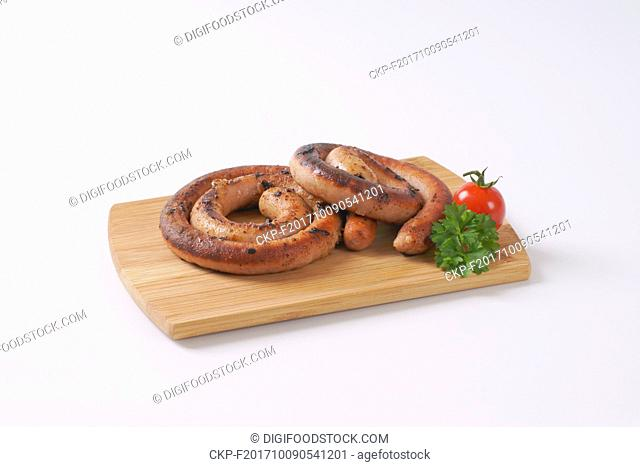 pan fried white wine pork sausages on wooden cutting board