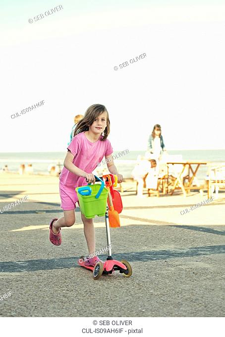 Young girl with bucket and spade on push scooter, Southwold, Sussex, UK