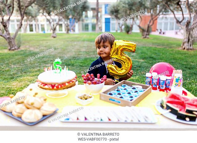 Little boy with golden balloon behind laid birthday table