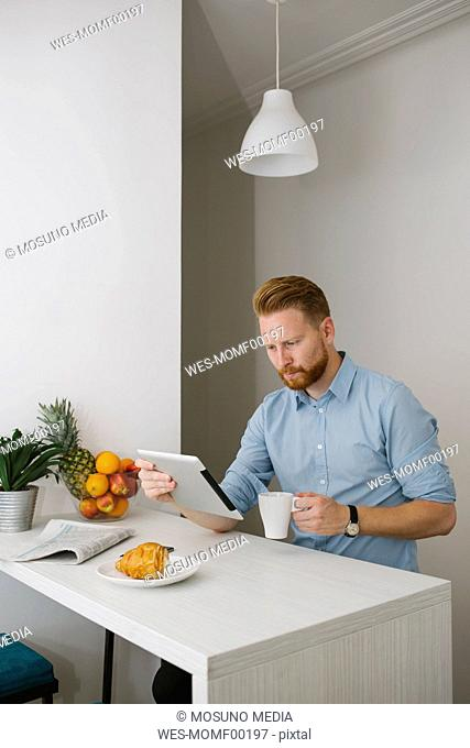 Businessman drinking coffee while using tablet at home