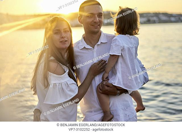 family, parenthood, sunset, candid, unposed, beach, seaside, real people. In holiday destination Chersonissos, Crete, Greece