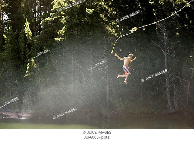 Boy 9-11, in swimming shorts, letting go of rope swing above lake, side view