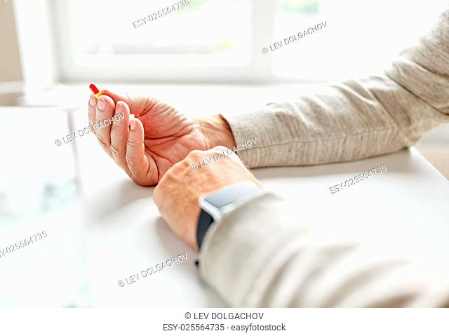 age, medicine, healthcare and people concept - close up of senior man hands with pill