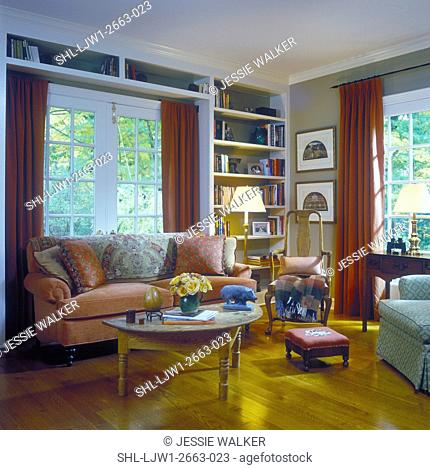 SITTING ROOMS - Traditional with French Country influence, coral couch with pillows, built in book shelves, french doors, red drapes, wood floor
