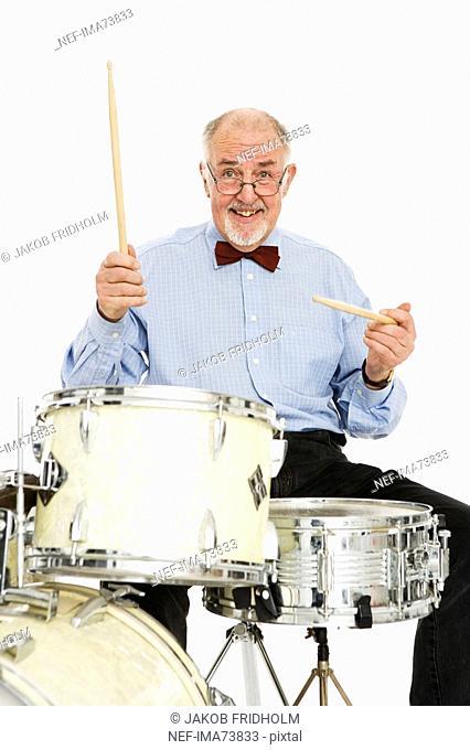 Senior man playing the drums
