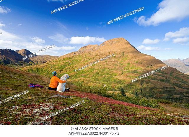 Mature woman hikes and enjoys scenery with dog on Old Womens Mountain, Kodiak, Southwest Alaska, Autumn