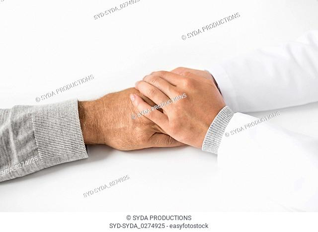 close up of doctor holding senior patient hand