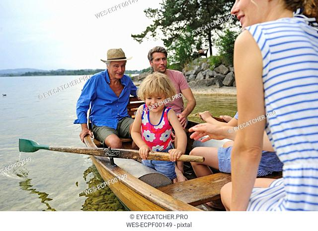 Germany, Bavaria, Murnau, happy little girl with her family in rowing boat at lakeshore