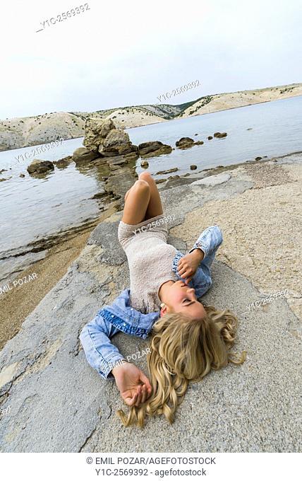 Fanciful young woman lying on back on seaside
