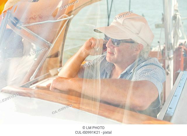 Mature man on cellphone on sail boat