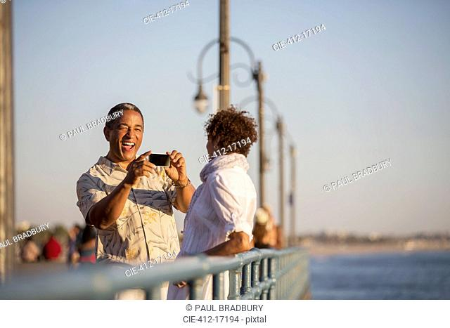 Man photographing woman on pier