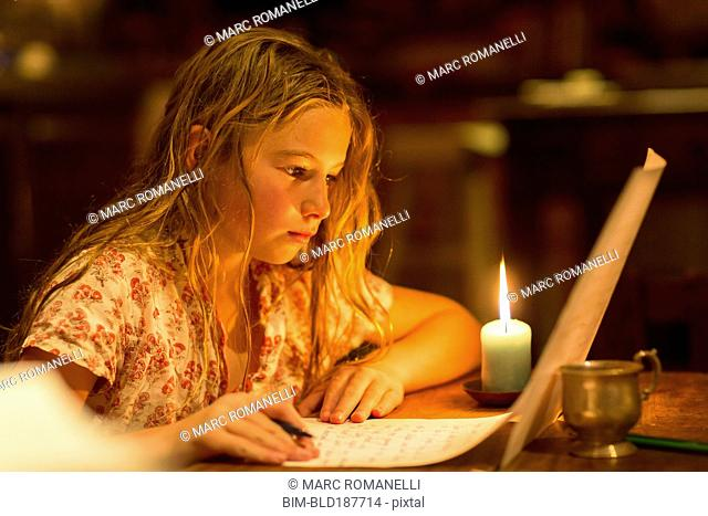 Caucasian girl writing by candle light