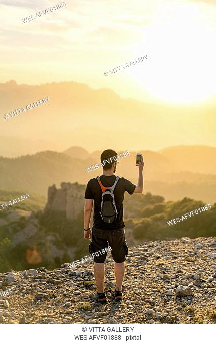 Spain, Barcelona, Natural Park of Sant Llorenc, man hiking and taking a picture of the view at sunset