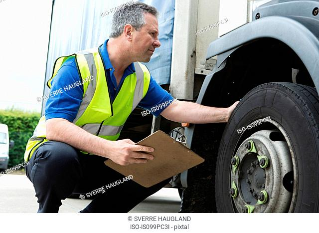 Man checking truck tire