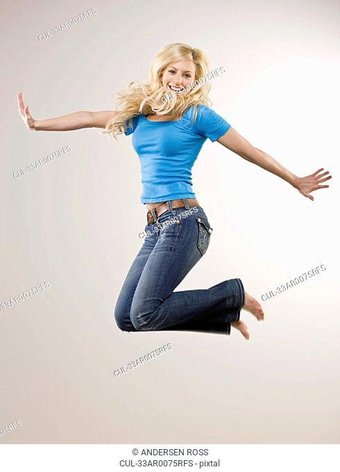 Smiling girl jumping in mid air