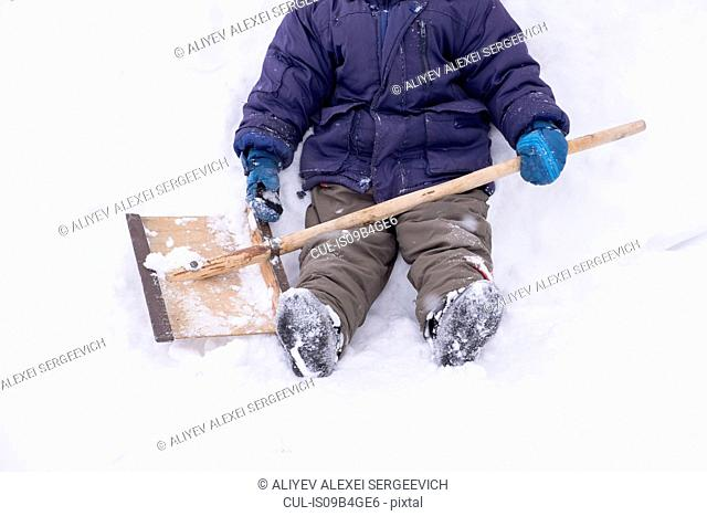 Baby boy sitting on snow with shovel