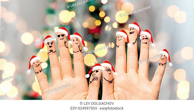 christmas, family, holidays, people and body parts concept - close up of two hands showing fingers in santa hats with smiley faces over lights background