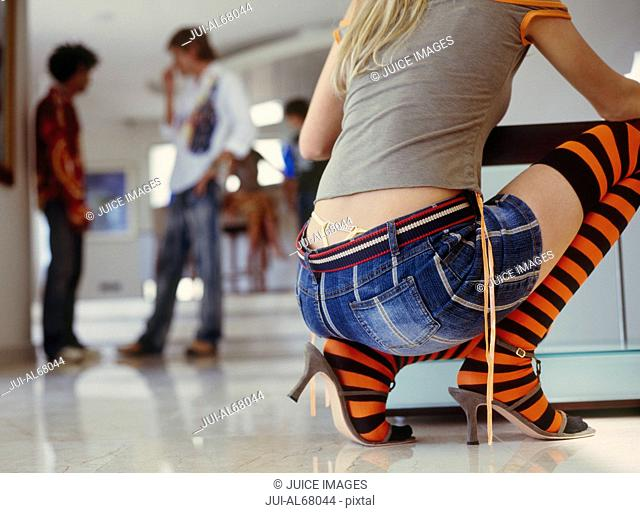Woman wearing striped knee-high socks crouching, friends talking in the background