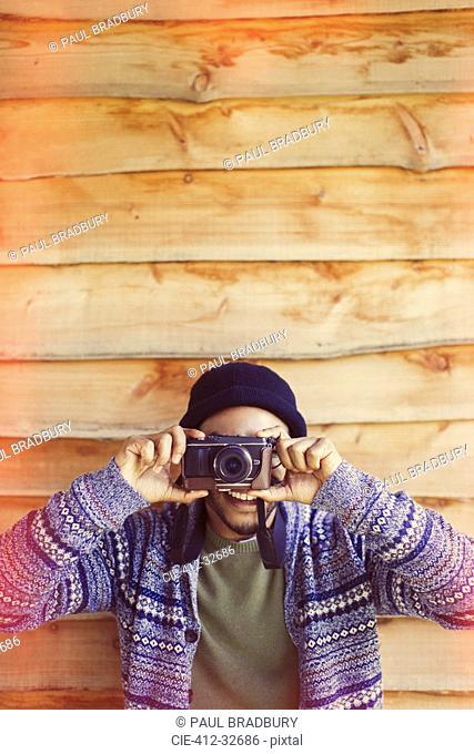 Portrait playful man using camera outside cabin
