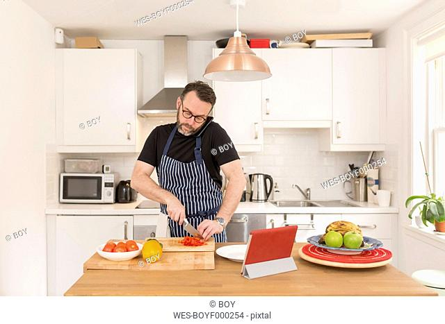 Man telephoning with smartphone while preparing vegetables in the kitchen