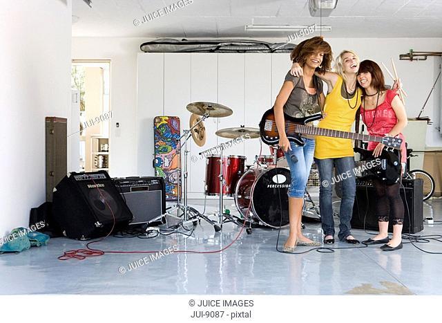 Three teenage girls 15-17 in garage band, smiling, portrait