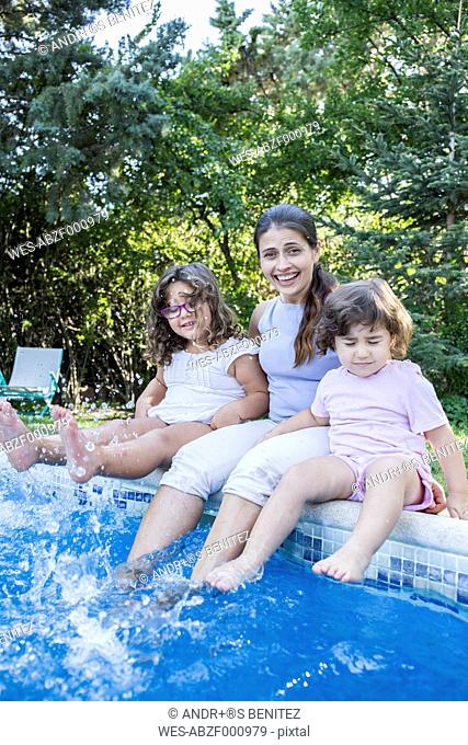 Portrait of smiling mother sitting on pool edge with her little daughters