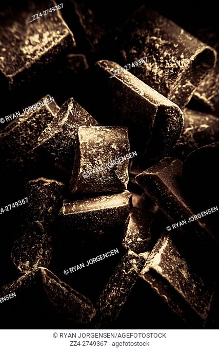 Close up still life sweets photo on a scattered mound of dark chocolate confectionary