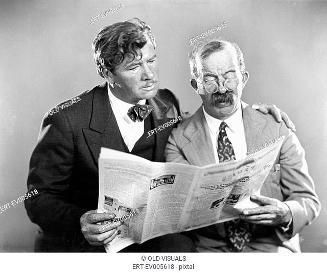 Two mature men reading a newspaper together All persons depicted are not longer living and no estate exists Supplier warranties that there will be no model...