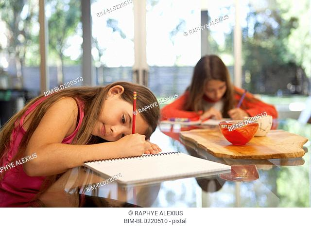 Mixed race sisters doing homework at table