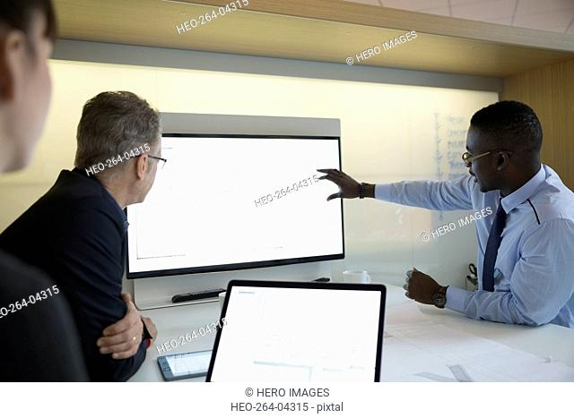 Architects discussing digital blueprint on monitor in meeting