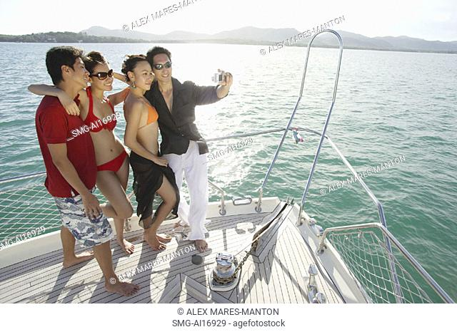 Young adults on boat deck, taking a picture