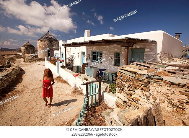 Woman in front of a Cyclades house and old windmills, Folegandros, Cyclades Islands, Greek Islands, Greece, Europe
