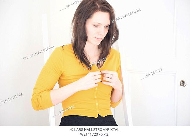 Serious woman undressing in home interior. Lifestyle image showing a pensive woman