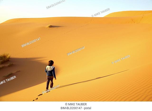 Mixed race boy walking in desert