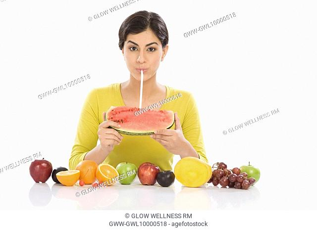Portrait of a woman drinking from a watermelon with a straw