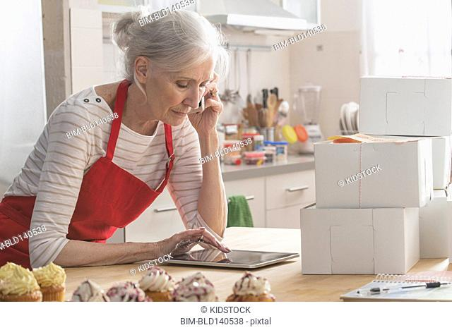 Older Caucasian woman with cupcakes and digital tablet