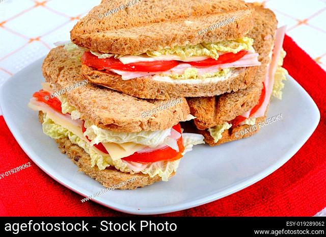 fresh and delicious classic club sandwich over a white glass dish