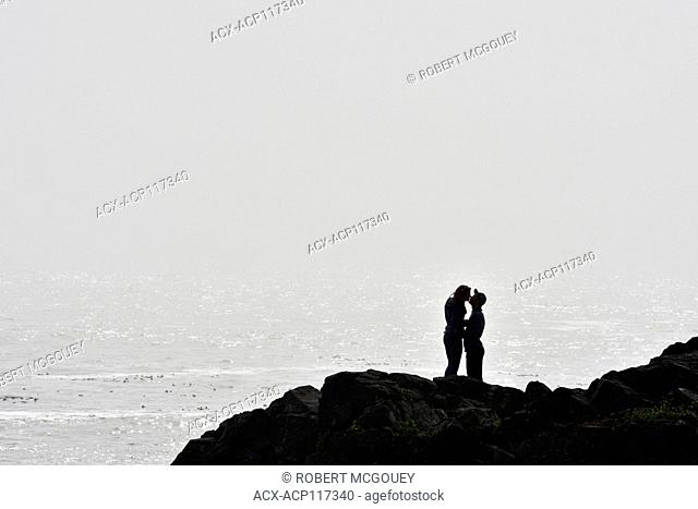 A silhoutte of a couple on the edge of the rugged shoreline share an embrace as the ocean fog rolls in , on the west coast Vancouver Island B.C
