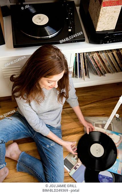Caucasian woman sitting on floor examining vinyl record