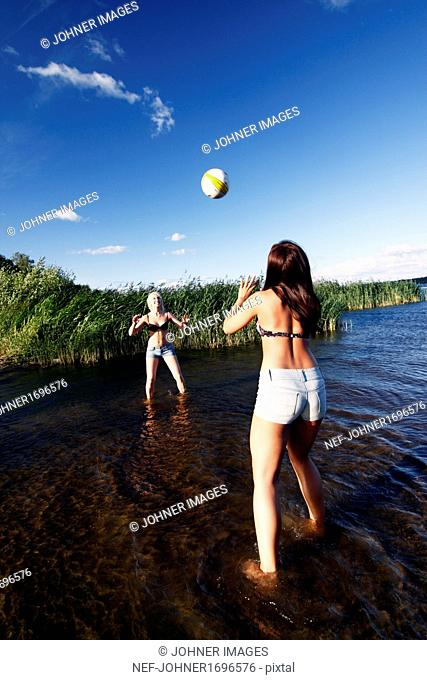 Women playing volleyball at water